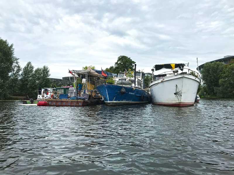 Mehrere Boote und eine Plattform schwimmen auf dem Wasser in der Rummelsburger Bucht auf der Spree in Berlin