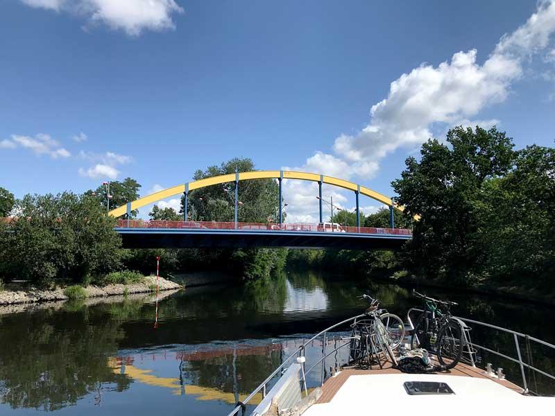 Eine blau und gelb gestrichene Autobrücke überspannt den Teltowkanal in Berlin
