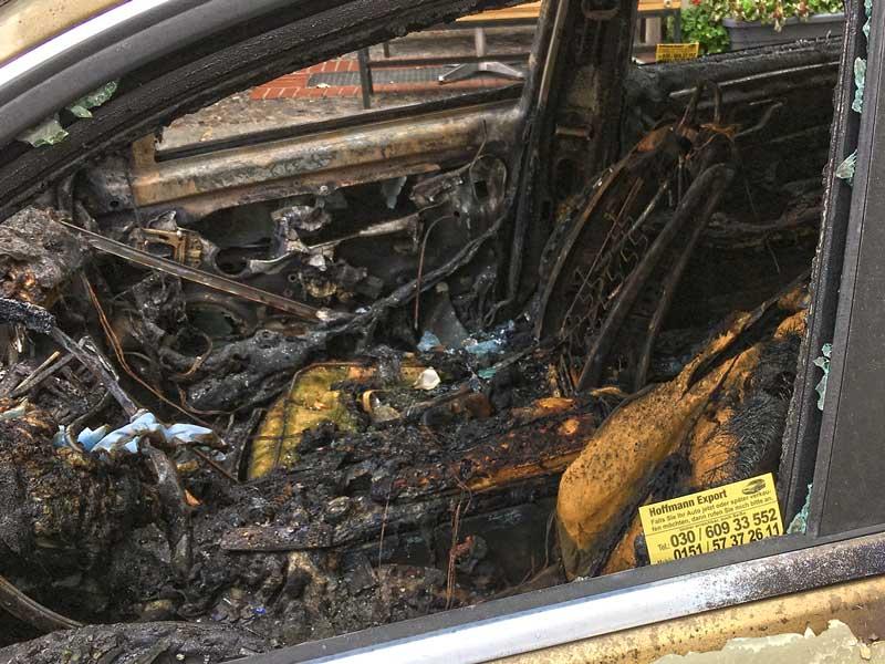 Im Fensterrahmen eines ausgebrannten Autos in im Bergmann Kiez in Berlin Kreuzberg steckt die Karte eines Händlers, der Fahrzeuge für den Export ankauft