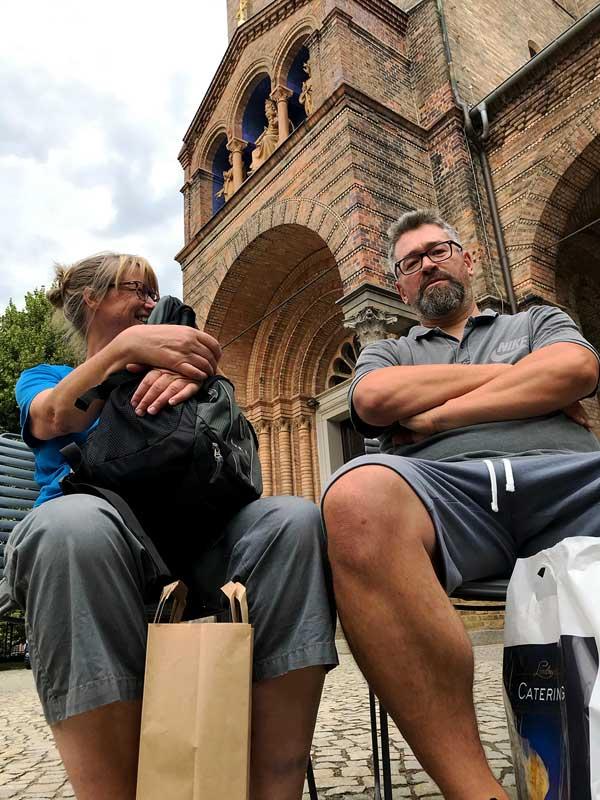 Die Eltern sitzen auf neuen Stühlen vor der Sankt Peter und Paul Kirche am Bassinplatz in Potsdam