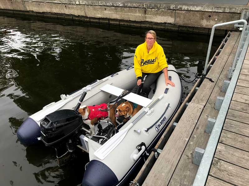 Barbara, die zwei englischen Bulldoggen und der schwarze Mops sitzen in einem Schlauchboot am Steg vor dem Schloss von Köpenick bei Berlin