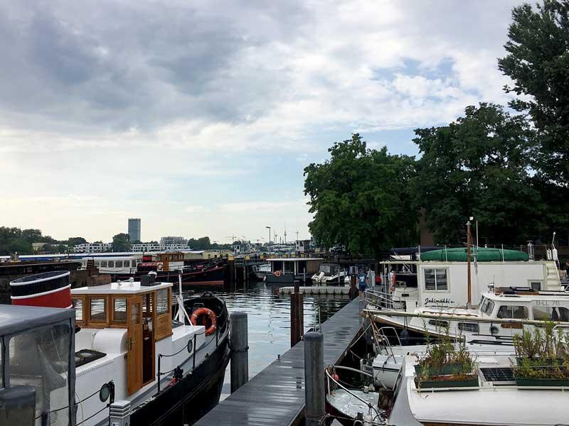 Blick von der Yacht aus über den Steg mit vielen anderen Booten, dahinter die Rummelsburger Bucht, Spree, Berlin. Ganz im Hintergrund kann man den Alex, das Wahrzeichen Berlins, erkennen