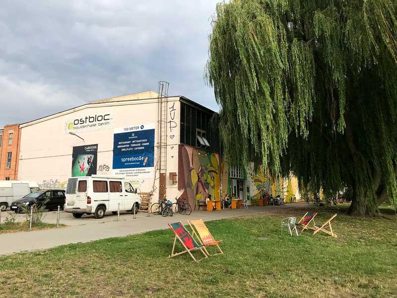 Die Boulderhalle ostbloc im Stadtteil Berlin Rummelsburg mit Freifläche an der Spree, großem Weidenbaum und Liegestühlen