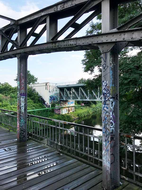 Mariendorfer Hafensteg, eine Brücke über den Teltow-Kanal zwischen Berlin Steglitz und Mariendorf, mit Blick auf die Eisenbahnbrücke, alles mit Graffiti verziert