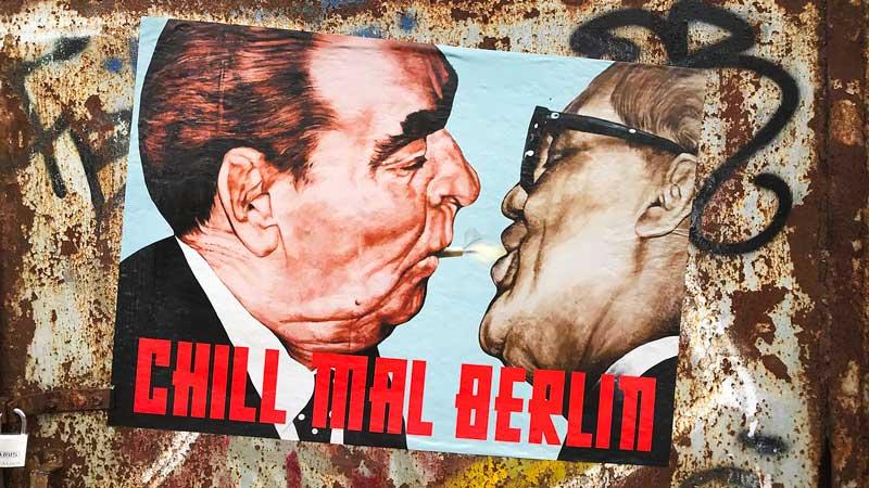 Eine grafische Darstellung des ikonischen sozialistischen Bruderkusses zwischen Breschnew und Honecker, allerdings mit einer Zigarette, klebt auf einem mit Graffiti verschmierten Metalltor in Berlin Friedrichshain