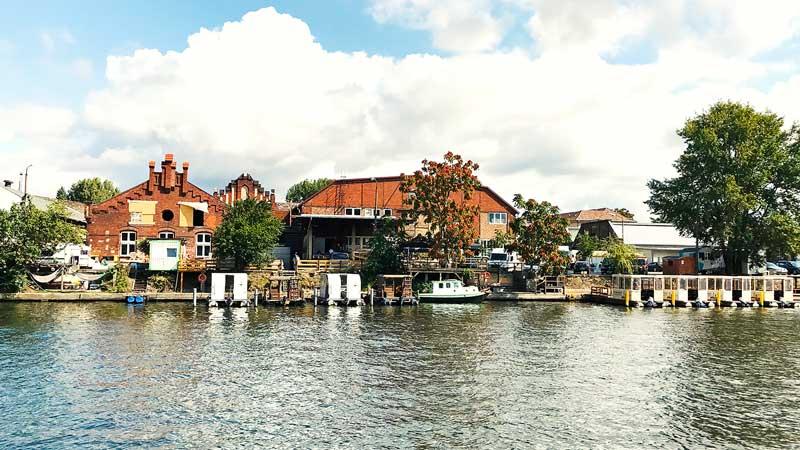 Uferbebauung mit alten Häusern aus Sichtziegel und Hausbootverleih am Ufer der Spree bei Berlin