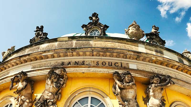 Blick nach oben auf den Schriftzug Sans Souci des gleichnamigen Schlosses in Potsdam