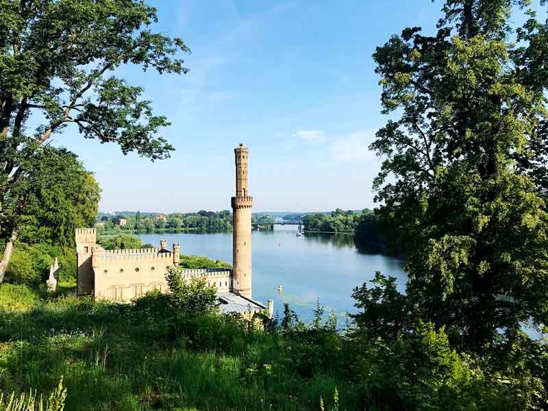 Blick von einer Anhöhe auf das alte Dampfmaschinenhaus im Park Babelsberg in Potsdam mit Glienicker Brücke im Hintergrund