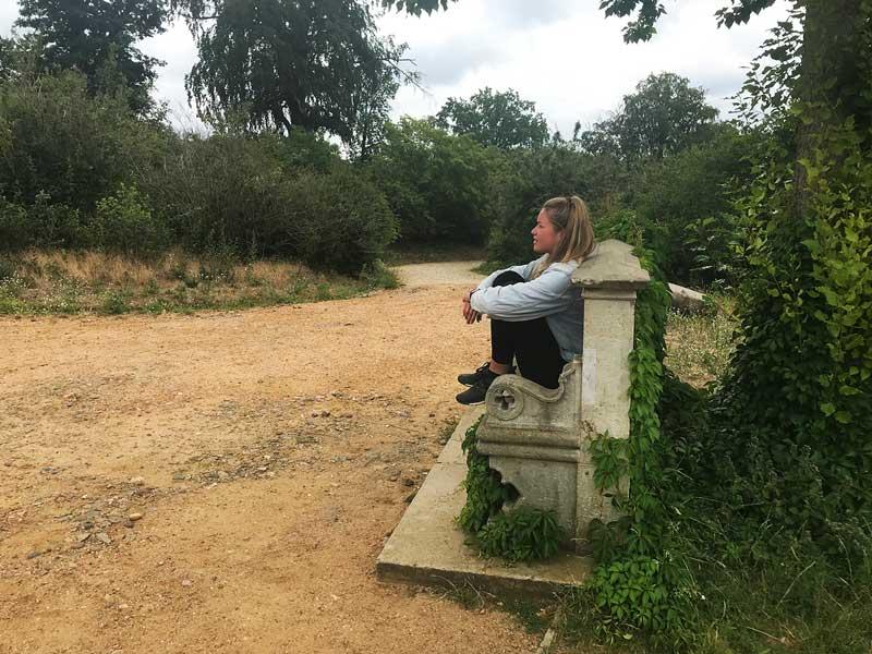 Die junge Frau sitzt auf einer alten Steinbank am Flatowturm und blickt über den Park Babelsberg in Potsdam an der Havel