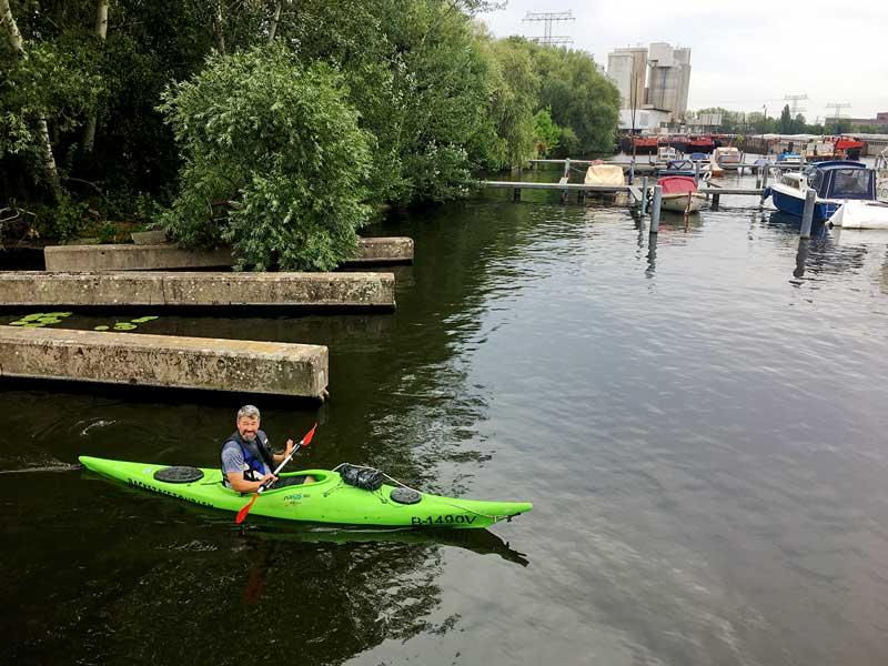 Thomas fährt mit einem Kajak auf dem Wasser vor dem Boot in der Rummelsburger Bucht auf der Spree in Berlin