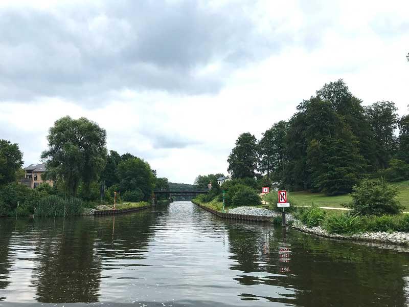 Die Durchfahrt vom Tiefen See in den Griebnitzsee ist sehr schmal und führt unter einer Brücke durch. Rechterhand reicht der Park Babelsberg Potsdam bis ans Ufer