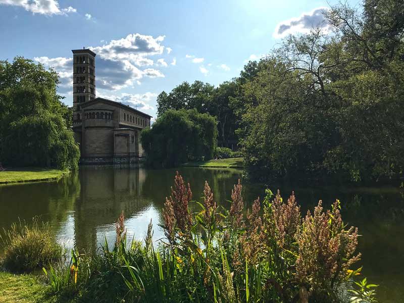 Die Friedenskirche im italienischen Stil mit Campanile an einem See mit Schilf und Bäumen im Park Sanssouci in Potsdam