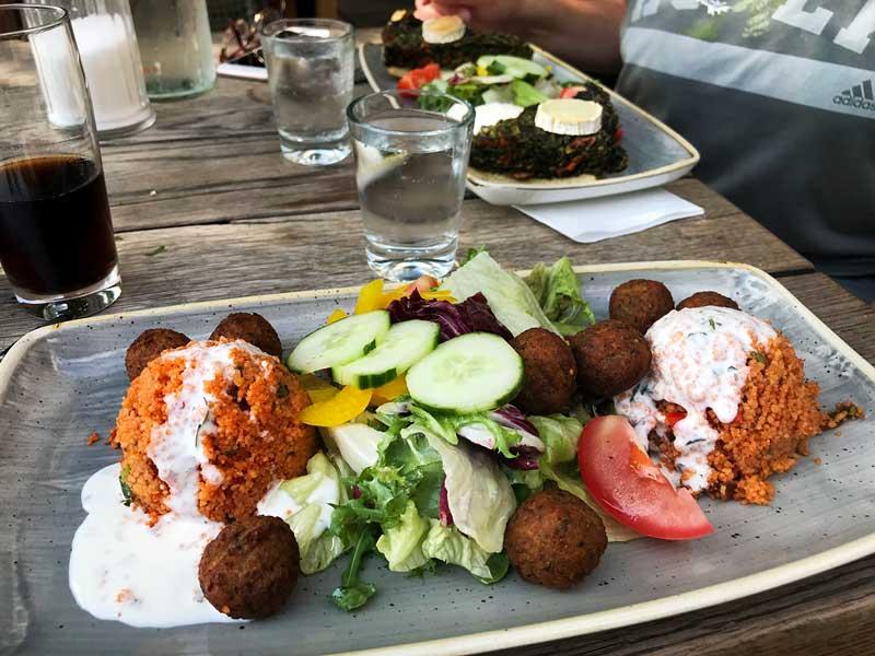 Ein Teller mit einem vegetarischen Gericht aus Quinoa, Falafel und Salat auf einem Tisch im Restaurant Hafenküche in der City Marina Rummelsburg auf der Spree in Berlin