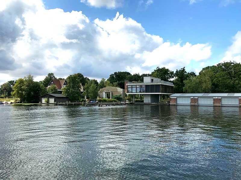 Modernes Wohnhaus aus Glas und Beton mit Bootshaus und Steganlagen am Ufer der Spree in Treptow
