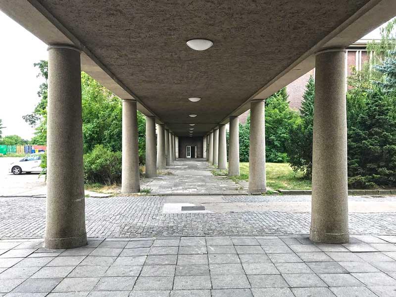 Ebenerdiger, überdachter, von Säulen getragener Verbindungsweg zwischen zwei Gebäuden des Funkhaus Berlin