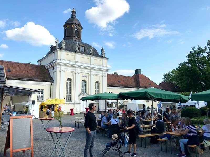 Verpflegungsstation mit Tischen und Bänken und eine Bühne mit Musiker sind im Schlosshof in Köpenick bei Berlin aufgebaut