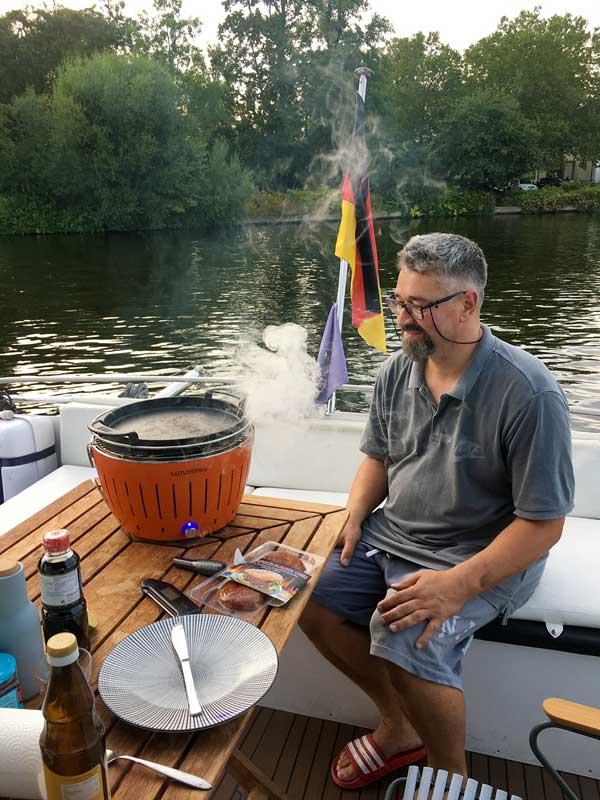 Thomas sitzt auf der Bank am Heck des Boots, auf dem Tisch der rauchende Lotusgrill, im Hintergrund die Schlossinsel von Köpenick bei Berlin