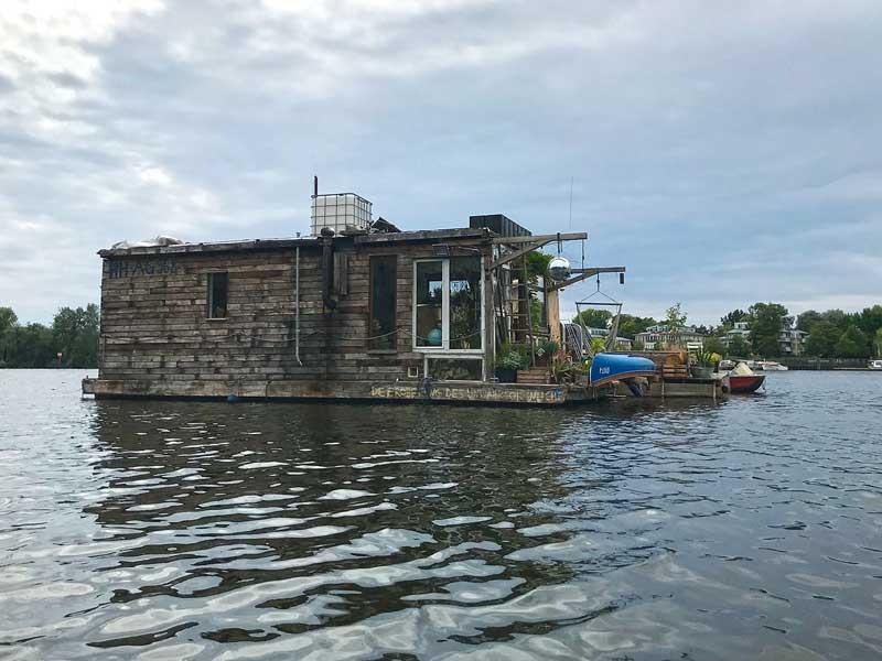 Ein romantisches Hausboot aus Holz ankert in der Rummelsburger Bucht auf der Spree in Berlin