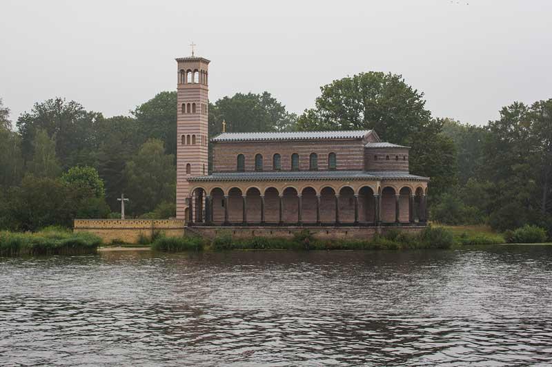 Am Ufer des Jungfernsee bei Sacrow in der Nähe von Potsdam liegt die italienisch anmutende Heilandskirche mit der gestreiften Fassade und den Bögen des Laubengangs direkt am Wasser