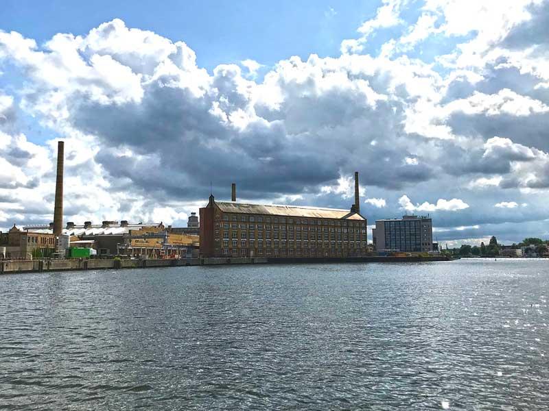 Gut erhaltenes altes Industriegebäude mit Schloten an der Spree in Oberschöneweide in Berlin, dahinter dramatische Wolken