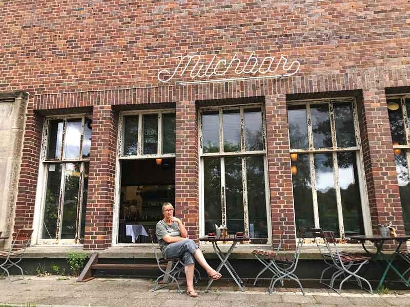 Barbara sitzt an einem Tisch vor der Milchbar, einem Cafe auf dem Gelände des Funkhauses Berlin vor einer schönen alten roten Ziegelfassade. Vor einem Fenster sind zwei Stufen für den Eingang