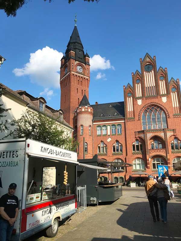 Verkaufsstände auf dem Stadtfest in Köpenick bieten Koblauchbaguette und Softeis an - im Hintergrund das Rathaus