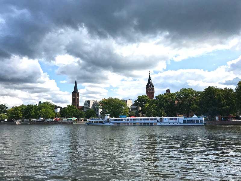 Stadtansicht von Köpenick bei Berlin vom Wasser aus mit Stadthafen und prägnanten Gebäuden Rathaus und Sankt Laurentiuskirche, im Vordergrund ein langes, niedriges Passagierschiff
