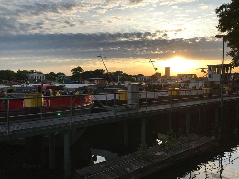 Die Sonne geht hinter alten Lastkähnen am Ufer der Rummelburger Bucht an der Spree in Berlin unter