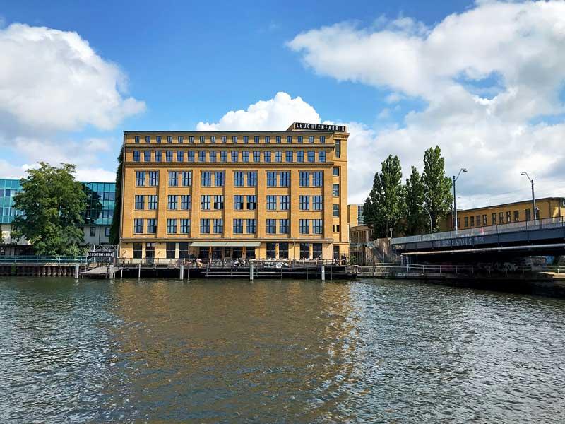 Renoviertes Industriegebäude aus gelbem Sichtziegel mit dem Schriftzug Leuchtenfabrik am Ufer der Spree in Niederschöneweide in Berlin