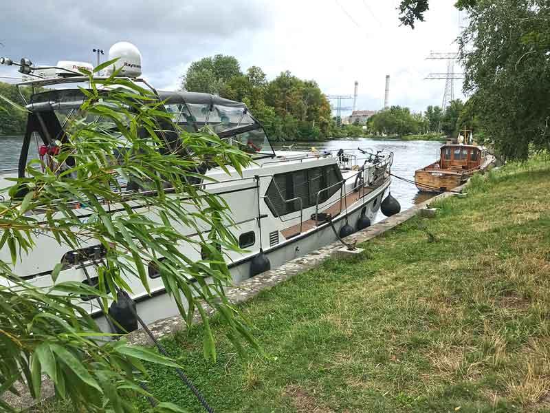 Das Boot liegt am grünen Ufer der Spree vor dem Funkhaus Berlin