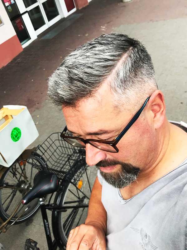Mann mit frischem Kurzhaarschnitt mit ausgeprägtem, rasiertem Scheitel und Bart