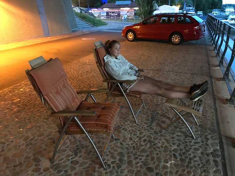 Die junge Frau sitzt auf einem Liegestuhl unter der Humboldtbrücke an der Havel in Potsdam
