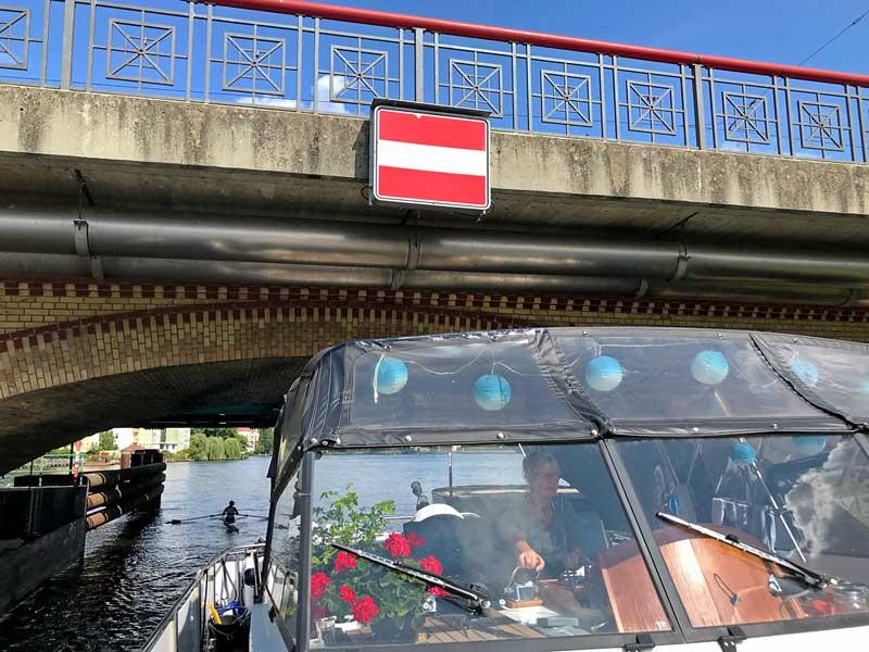 Blick vom Bug aus auf den Steuerstand und die Brücke: Barbara steuert das Boot unter einer niedrigen Brücke hindurch - Lange Brücke auf der Spree in Köpenick bei Berlin