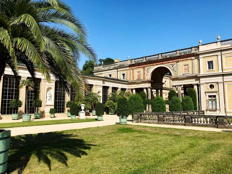 Orangerie-Schloss: Schloss im italienischen Stil mit Palmen und großen Fenstern im Park Sanssouci in Potsdam