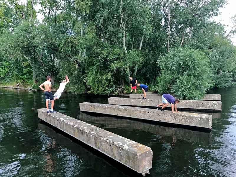 Parkour Sportler der Gruppe Ashiguru Parcour & Freerunning um Benni Grams trainieren auf Betonklötzen im Wasser hinter der City Marina Berlin Rummelsburg an der Spree