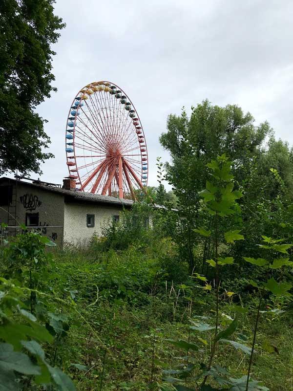 Ein großes altes Riesenrad in orange ragt im verwilderten Spreepark in Treptow in Berlin hinter einem Haus empor