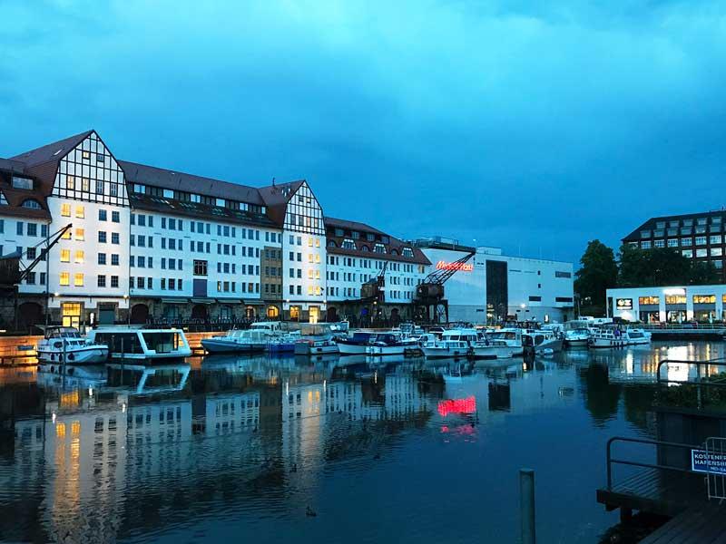 Blick auf das ehemalige Lagerhaus des Tempelhofer Hafens in Berlin in der Abenddämmerung. Die Lichter der Geschäfte und Restaurants spiegeln sich im Wasser des Hafenbeckens