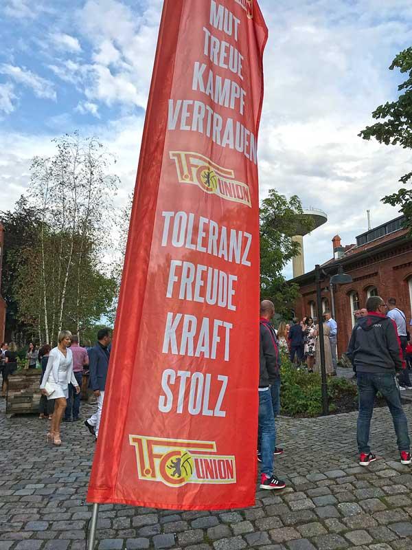 Fahne von Union Berlin vor einem Veranstaltungsgebäude im Marienpark in Berlin Mariendorf, die auf eine Veranstaltung des Fußballclubs hinweist. Die Gäste sind teilweise schick gekleidet