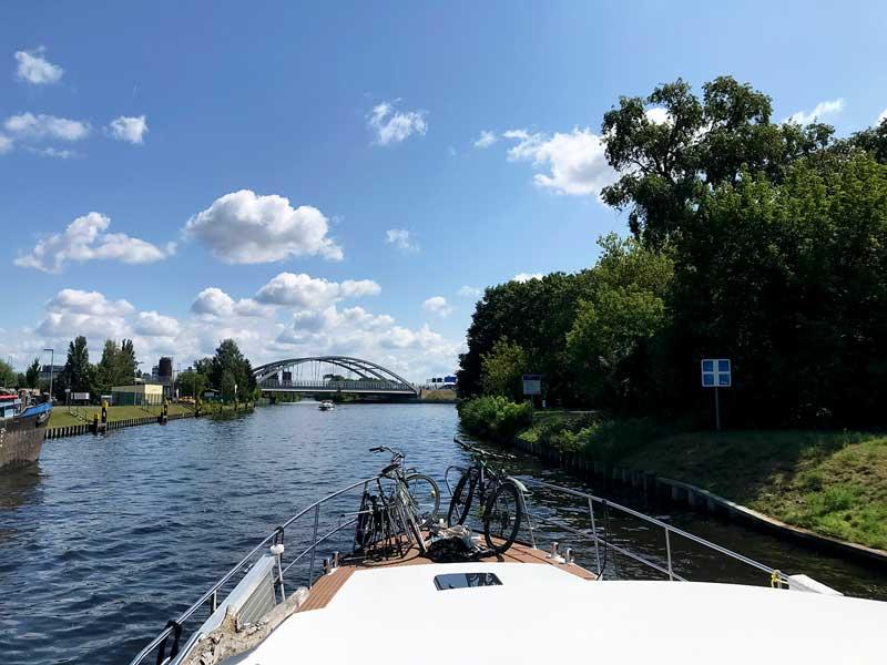 Das Schiff fährt auf eine Wasserstrassenkreuzung auf dem Teltowkanal in Berlin Neukölln zu