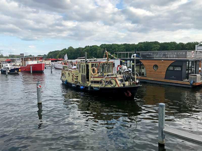 Ein hübsches altes Wohnboot fährt in den Hafen City Marina Berlin Rummelsburg an der Spree ein