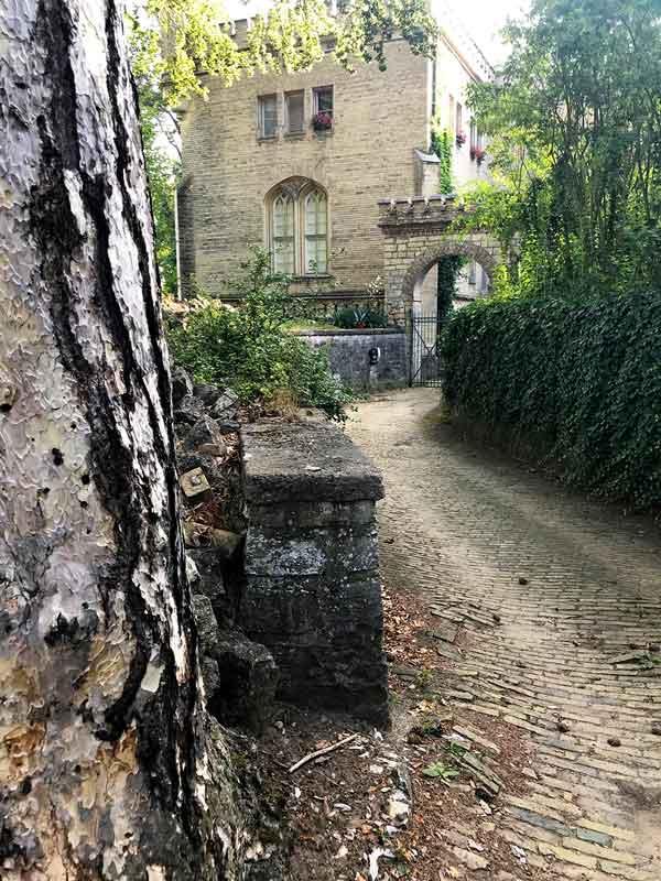 Kleiner Weg mit Kopfsteinpflaster führt zu einem historischen Bauwerk, die ehemalige Schlossküche des Schlosses Babelsberg in Potsdam