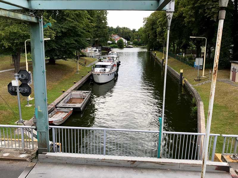 Blick von der Brücke über die Dahme-Wasserstraße auf die Zugbrücke und mehrere Sportboote, die auf die Schleusung in der Schleuse Neue Mühle in Königs Wusterhausen, Brandenburg, südlich von Berlin warten.