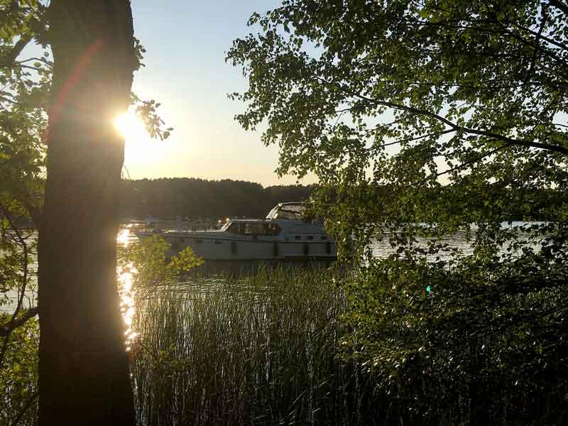 Blick durch den Wald und über den Schilfgürtel auf das ankernde Boot bei untergehender Sonne auf dem Schmöldesee, Brandenburg, Dahme-Wasserstraße südlich von Berlin