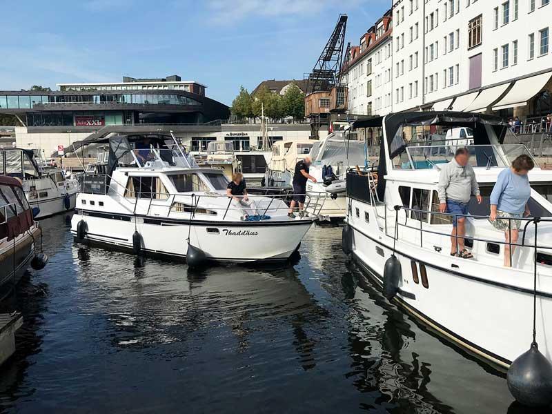 Mann auf Charteryacht hält mittels eines Bootshakens Abstand von einem anderen Boot im Tempelhofer Hafen Berlin