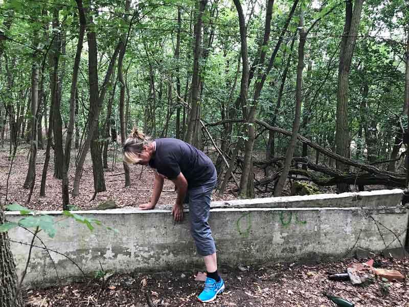Frau klettert über zusammengebrochene Betonmauer im Wald