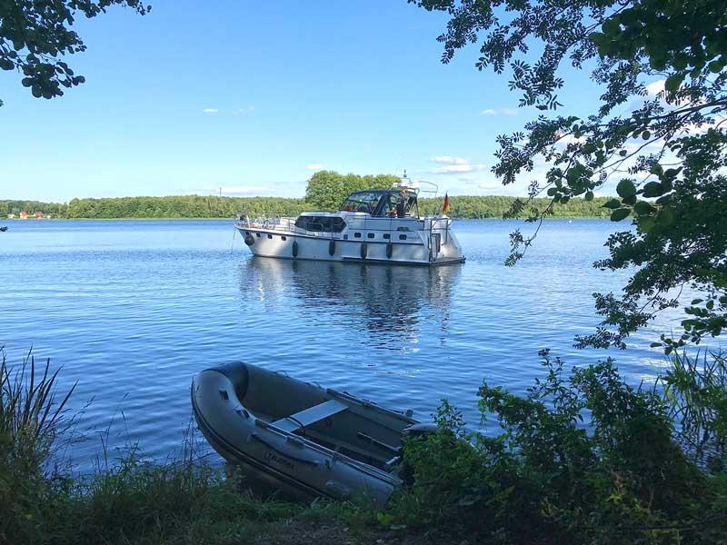 Die Motoryacht liegt unweit des Ufers vor Anker, im Vordergrund das Beiboot, im Klein Köriser See, Teil der Dahme-Wasserstraße und der Teupitzer Gewässer in Brandenburg, südlich von Berlin