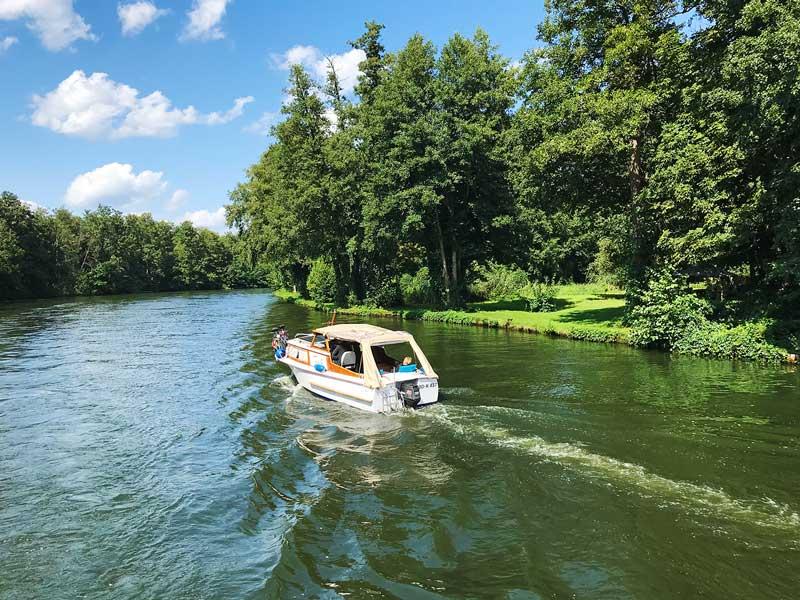 Vor uns fährt ein kleines Sportboot auf der Dahme, die die Seen der Seenkette verbindet. Dahme-Wasserstraße, Brandenburg, südlich von Berlin