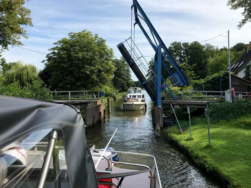 Blick zurück auf die geöffnete Zugbrücke über den Kanalgraben in den Teupitzer Gewässern, Brandenburg, Dahme-Wasserstraße südlich von Berlin. Man sieht, dass die Durchfahrtshöhe und -breite auch bei geöffneter Brücke eingeschränkt sind aufgrund des Hebewinkels