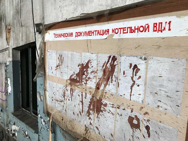 Ein Anschlagbrett mit Aushängen in russischer Sprache ist mit Spitzern überzogen, die wie getrocknetes Blut aussehen. Landesirrenanstalt Teupitz, Brandenburg, südlich von Berlin - Lost Places