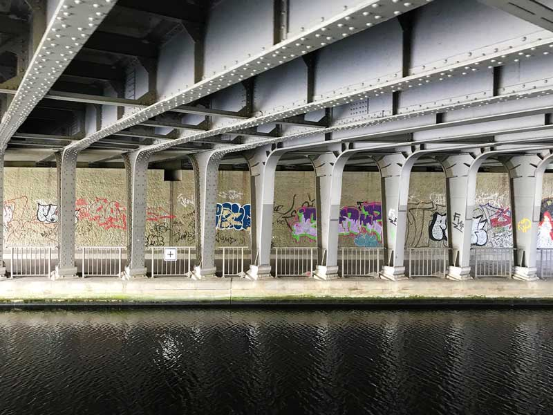 Unter einer Stahlbrücke über den Teltowkanal in Berlin mit Stahlträgern und Grafitti
